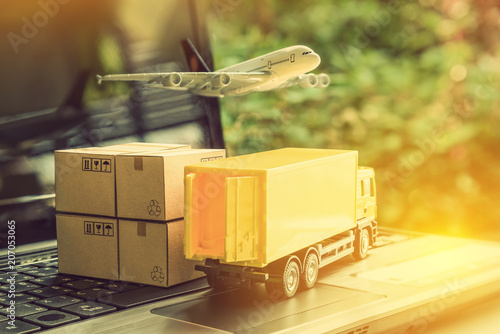 Fotomural  Air courier / freight forwarder or shipping service concept :  Boxes, a truck, white plane flies over a laptop, depicts customers order things from retailer sites via the internet and ship worldwide