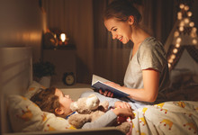 Mother And Child Reading Book In Bed Before Going To Sleep .