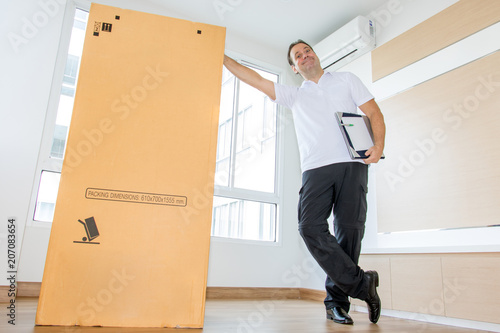 Obraz A man standing beside a large package in an empty room. The postman delivers the parcel to the new apartment. - fototapety do salonu