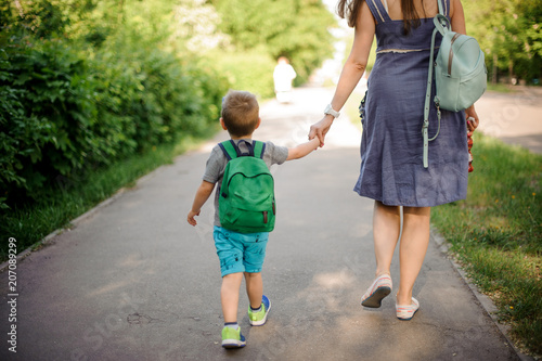 Back view of mother walking down the street with a little son with a backpack on sunny day