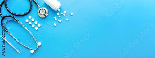 Fotografía Pills and medical equiupments on light blue banner background