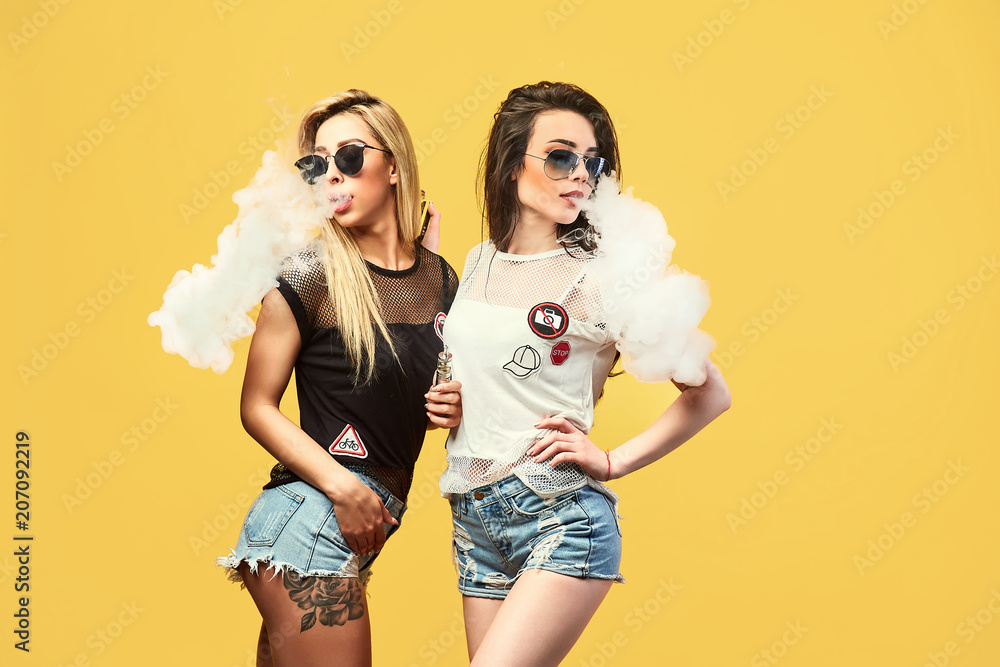 Fototapety, obrazy: Side view of trendy young female in glasses and shorts standing and smoking on studio background