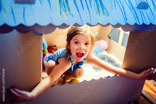 Fotografia, Obraz Content pretty little girl sitting inside of colored carton playhouse looking at camera smiling through small window