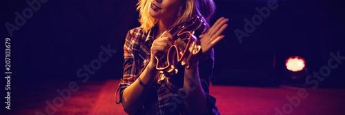 Obraz na płótnie Portrait of woman playing tambourine at nightclub