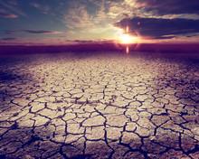 Paisaje Desértico Y Nubes De Tormenta.Suelo Agrietado Y Puesta De Sol.Calentamiento Global Y Cambio Climático
