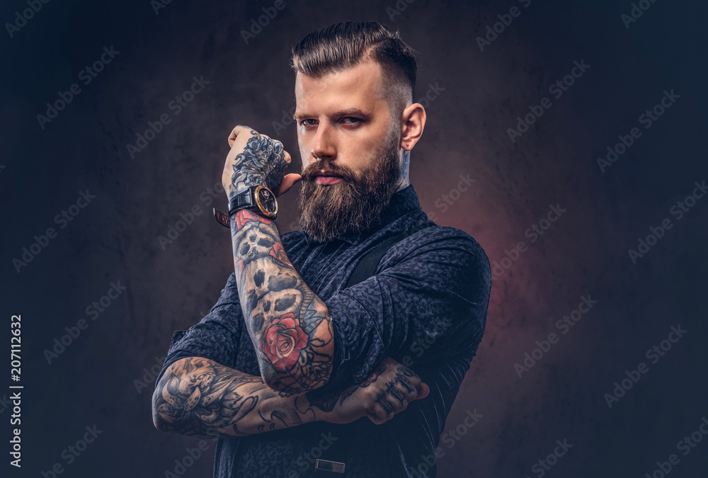 Fototapeta Pensive old-fashioned hipster in a blue shirt and suspenders, standing in a studio.