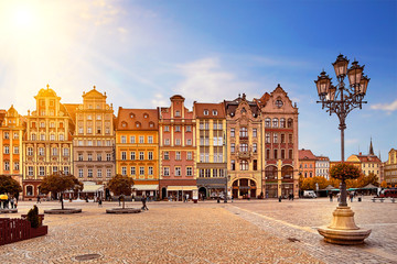 Central market square in Wroclaw Poland with old colourful houses, street lantern lamp and walking tourists people at gorgeous stunning morning sunrise sunshine. Travel vacation concept