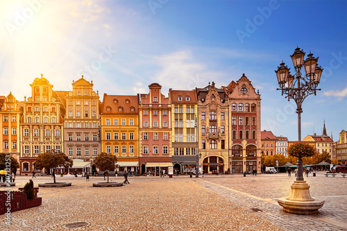 Fototapeta Central market square in Wroclaw Poland with old colourful houses, street lantern lamp and walking tourists people at gorgeous stunning morning sunrise sunshine. Travel vacation concept obraz