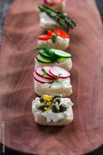 Set of different mini sandwiches on a wooden board.