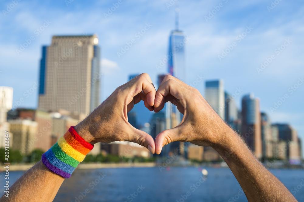 Fototapeta Hands wearing pride rainbow wristband making heart symbol