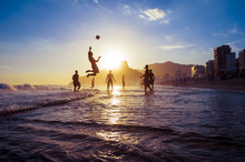 Sunset Silhouettes Playing Keepy-uppie Beach Football On The Sea Shore In Ipanema Beach Rio De Janeiro Brazil