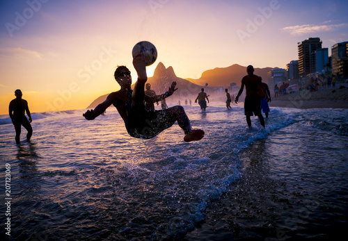 sunset silhouettes playing keepy-uppie beach football on the sea shore in Ipanem Canvas Print