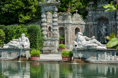 Poster Historisch mon. Marlia, Lucca, Italy - 2018, May 25: The Villa Reale Lemon garden with large ornamental pool and stone balustrade; two statues of Giants representing the local rivers Arno and Serchio.