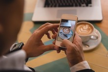 Businessman Clicking Photo Of Coffee In Coffee Shop