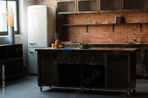 Fototapeta Dark loft kitchen with red brick wall. Kitchen table Cutlery, spoons, forks, breakfast fruit, fridge. Morning natural sunlight obraz