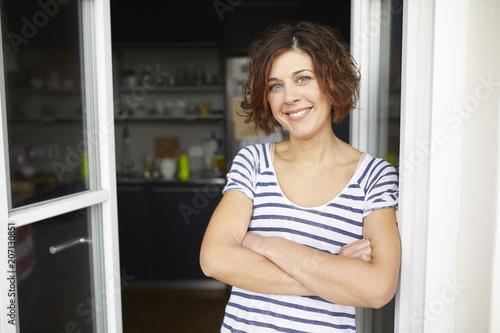 Portrait of content mature woman leaning against open balcony door