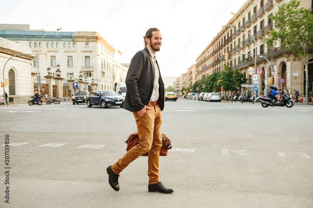 Fototapety, obrazy: Portrait of modern elegant man in stylish clothing laughing, while walking across the road in city street with leather male bag in hand