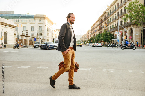 Fototapeta Portrait of modern elegant man in stylish clothing laughing, while walking across the road in city street with leather male bag in hand obraz