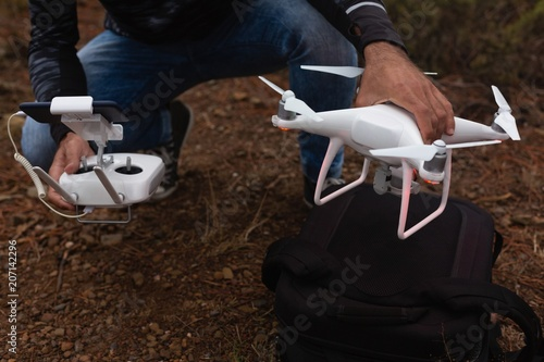 Man holding a flying drone and remote control
