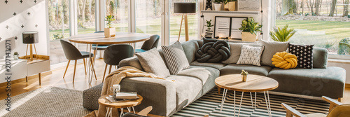 Obraz Side angle of a corner sofa with pillows, table and dining table with chairs behind in a bright living room interior - fototapety do salonu