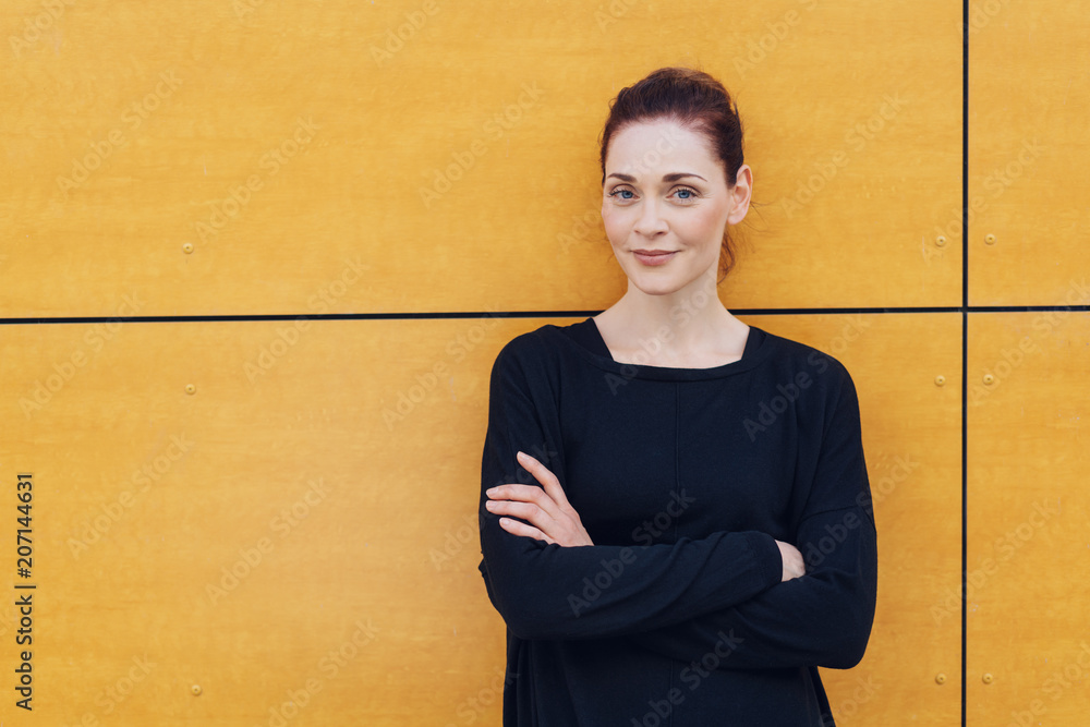 Fototapety, obrazy: Smiling woman with folded arms against urban wall