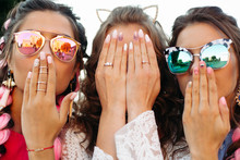Close Up Of Three Young Girls Wearing In Sunglasses Hiding Face By Hands.