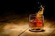 Leinwanddruck Bild - Whiskey splash in glass on a wooden table.