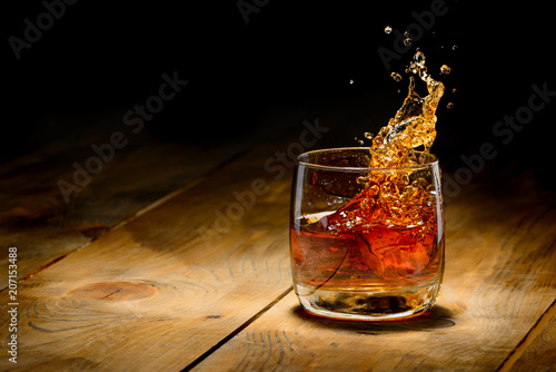Photo Whiskey splash in glass on a wooden table.
