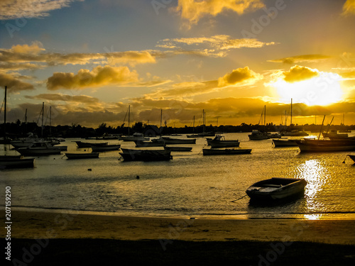 Spectacular sunset over the ocean with boats in the calm waters of the Grand Baie, Mauritius, Indian Ocean, Africa.