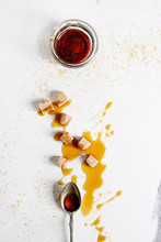 Homemade Liquid Transparent Brown Sugar Caramel In Glass Jar With Spoon And Cane Sugar Cubes Over White Marble Background. Flat Lay, Space.