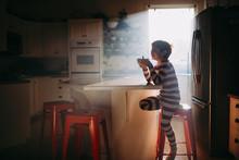 Boy Sitting In Kitchen Eating ...