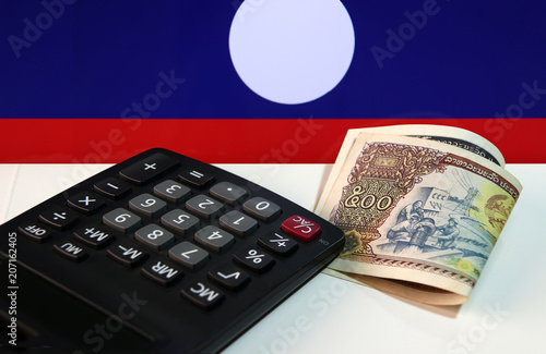 Recess Fitting Chicken Five hundreds of banknote currency Lao Kip with calculator on the white floor with Laos nation flag background. It is the money of Laos in 1988, and the concept of finance.