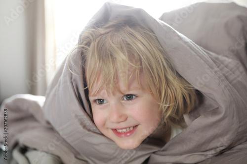 Fotografie, Obraz  Petit garçon se cache sous la couverture