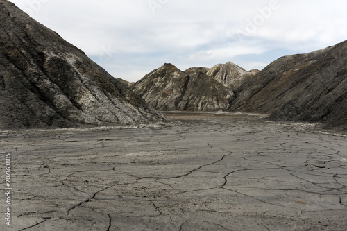 landscape - view from the bottom of a dry desert canyon with a sandy-clay bottom and weathered slopes