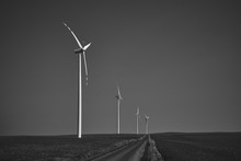 Black And White Landscape With Wind Turbines Standing On A Secluded Empty Field With A Road In The Middle, Windmill For Electric Power Production, Wind Turbines Generating Green Energy Electricity