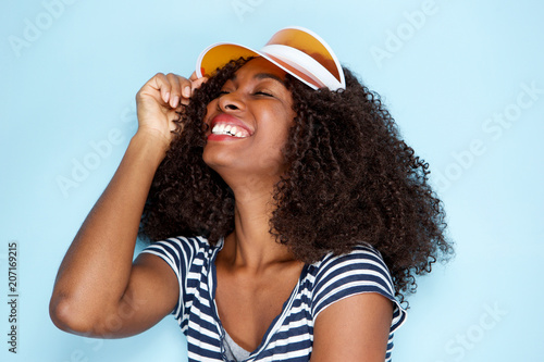 Photo  cheerful african woman wearing cap and smiling on blue background