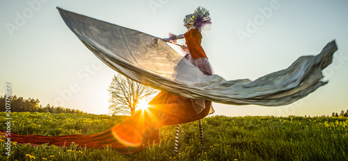 Fotografie, Obraz  Fairy tale woman on stilts with silver flag in bright fantasy stylization