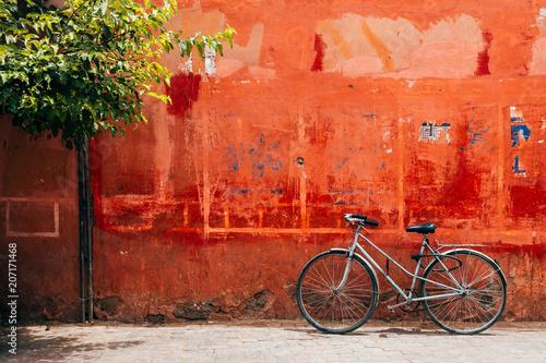 Foto op Aluminium Fiets old bike standing at red wall