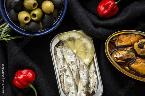 Peppers and olives near canned fish