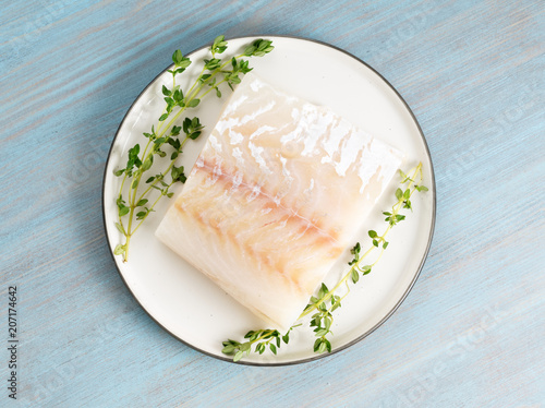 Foto piece of raw cod fish fillet on plate on blue wooden table, top view