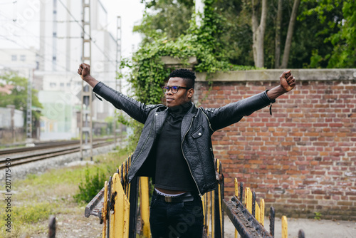 Young black man standing at street with hands up