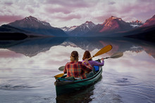 People On Kayak Paddling Into Serene Beautiful Lake With Perfect Reflection Of Mountains During Summer Sunset