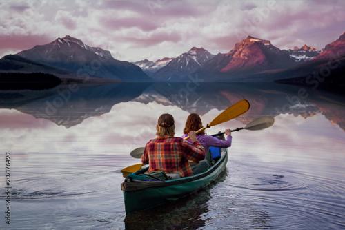 Valokuva  People on kayak paddling into serene beautiful lake with perfect reflection of m