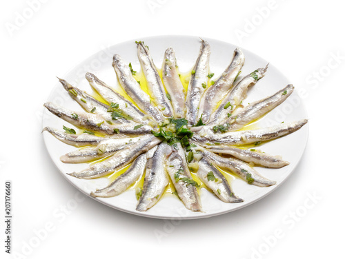 Delicate Marinated anchovies with parsley, olive oil and vinegar isolated on white background.