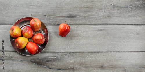 Fotografía  Teble top view (wide, right side is space for text) of red ripe glossy apples in metal bowl, placed on gray wood desk