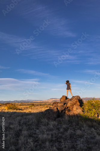 Fotobehang Grijze traf. woman standing on top of a rock pile in the desert, looking out towards mountains in the distance