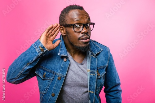 фотографія  Deaf African man with glasses brought his hand to his ear to hear better standin