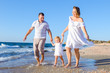 Happy family of three - pregnant mother, father and daughter holding hands and having fun walking on the beach. Family vacation, travel concept. Bright sunlight. Copy space.