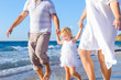 Happy child girl with parents holding hands and having fun walking on the beach. Family vacation, travel concept. Bright sunlight. Copy space.