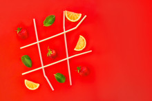 Tic Tac Toe Game Made Of Cocktail Straws, Strawberry, Mint And Lemon Slices On Bright Red Background With Copy Space. Lemonade, Summer Drinks. Minimal Food Concept. Selective Focus.